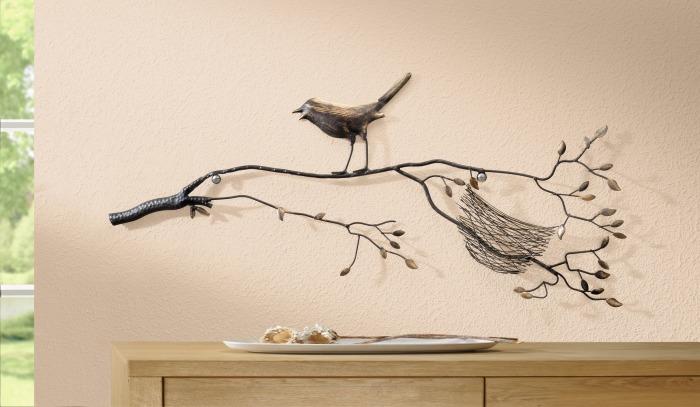 Декоративная птица из кованного железа сидящая на ветке.