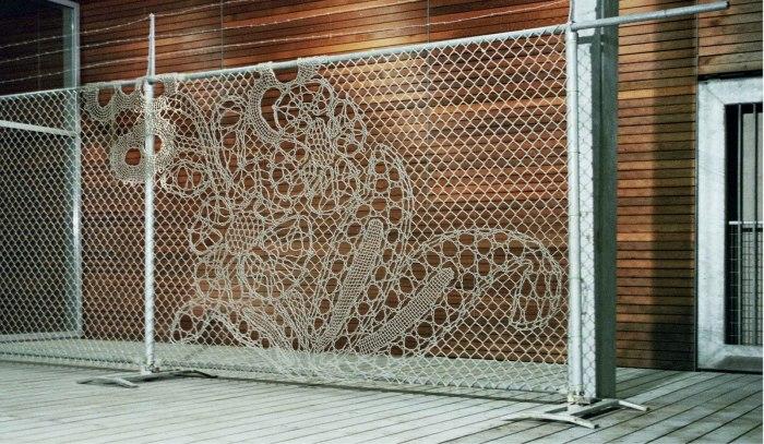 Фантастический забор из сетки рабицы, украшенный узорами, которые выполнены относительно новой техникой плетения без пайки и литья.