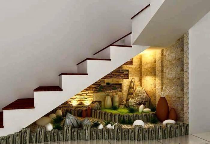 Маленький искусственный садовый участок под лестницей.