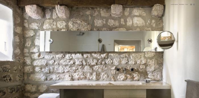 Каменные стены просто отлично сочетаются со грубыми потолочными балками в ванной комнате.