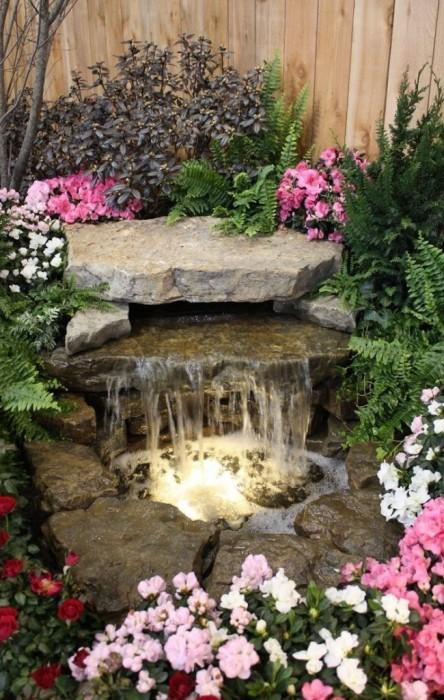 Маленький искусственный водоём с водопадом в окружении яркой цветочной композиции.