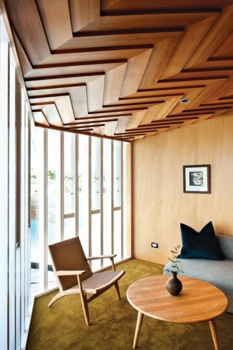 Потолок с отделкой деревянными панелями смотрится красиво и необычно.