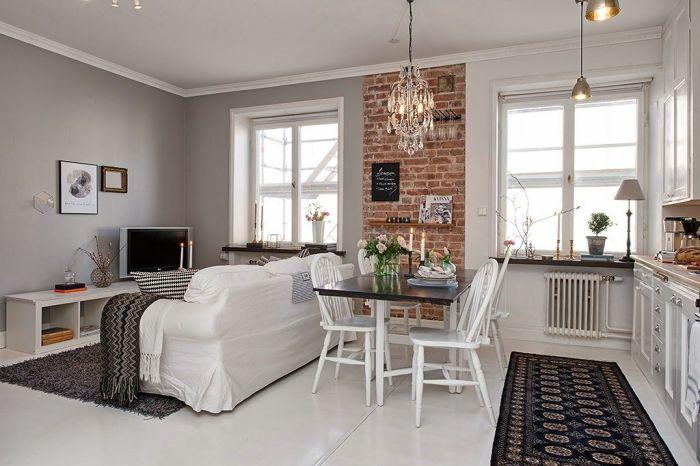 Декоративная кирпичная стена в современном интерьере однокомнатной квартиры.