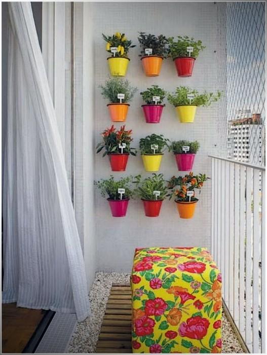 Разноцветные цветочные горшки на стене – очень стильное и нестандартное решение для балкона.