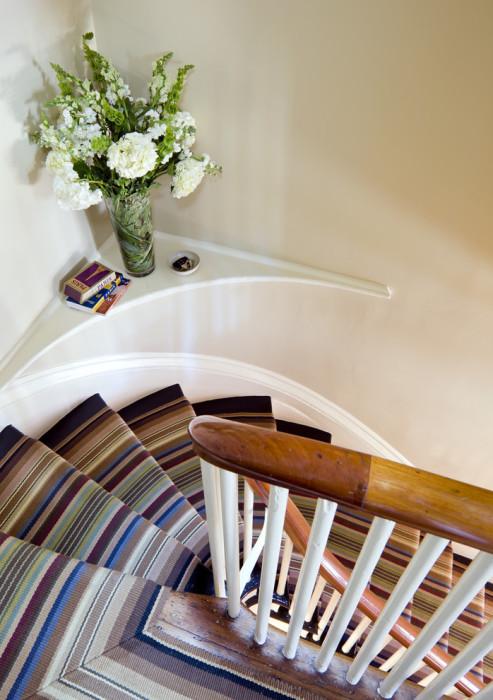 Деревянная лестница ступеньки которой обшиты яркой ковровой дорожкой ручной работы.