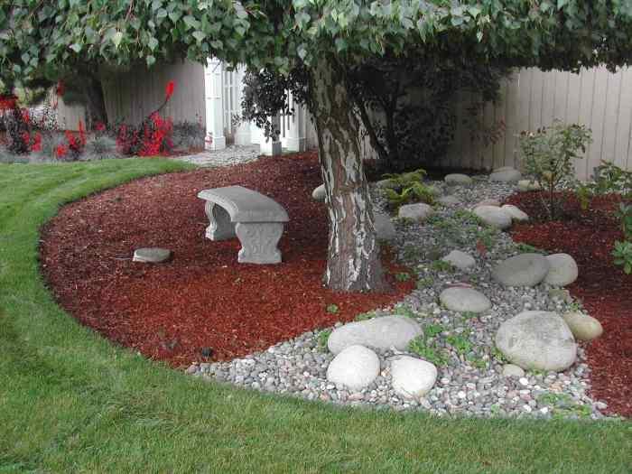Оригинальное сочетание каменных конструкций с зелеными растениями и цветами.