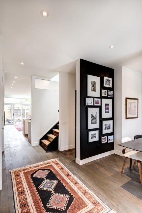Черная стена в светлой комнате - отличное место для настенной галереи.