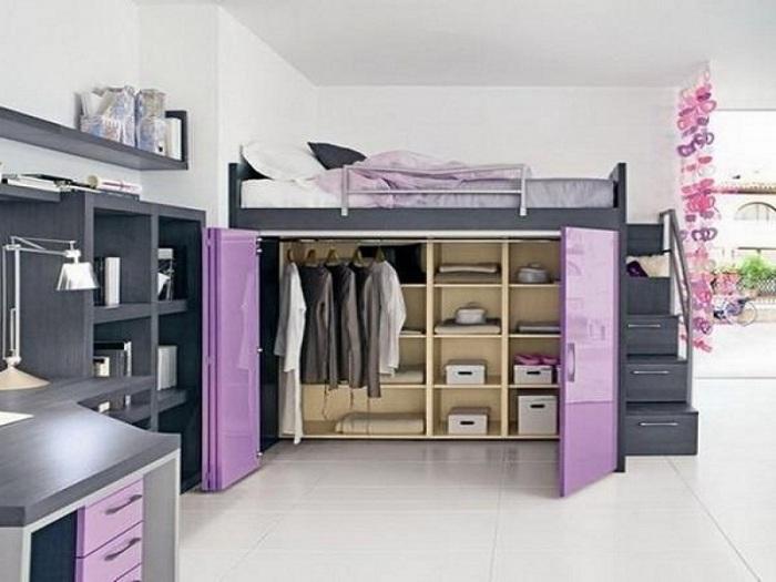 Узкая кровать, расположенная над просторной гардеробной с множеством деревянных полочек.