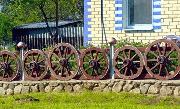 Необычный и стильный забор из старых деревянных колёс, который сразу привлечёт внимание гостей.