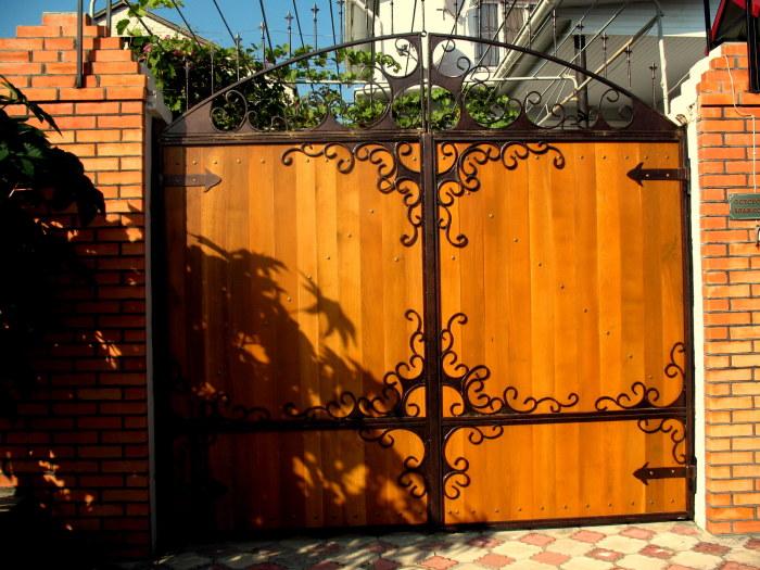 Кованная конструкция ворот обшитая дорогим деревом.
