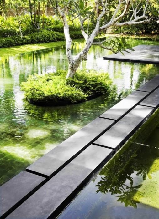 Декоративный пруд геометрически правильно формы с каменной дорожкой по центру.