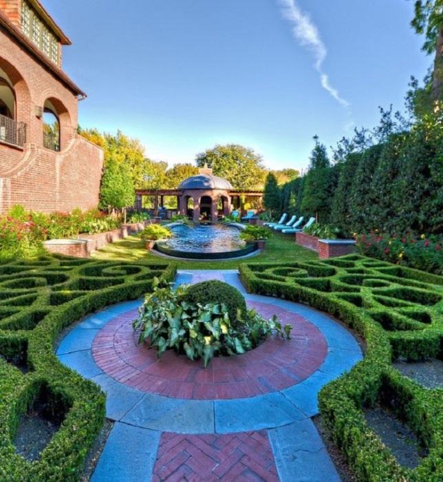 Профессионально оформленный ландшафт перед загородным домом с зелеными насаждениями и водоемом позволит создать вокруг себя эксклюзивное пространство.