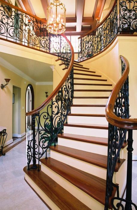 Лестница с кованными перилами изготовленная из натуральной породы древесины и метала.