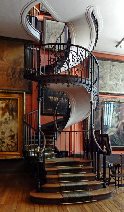 Спиралевидная лестница из кованного метала и теплого дерева гармонично впишется в современный интерьер.