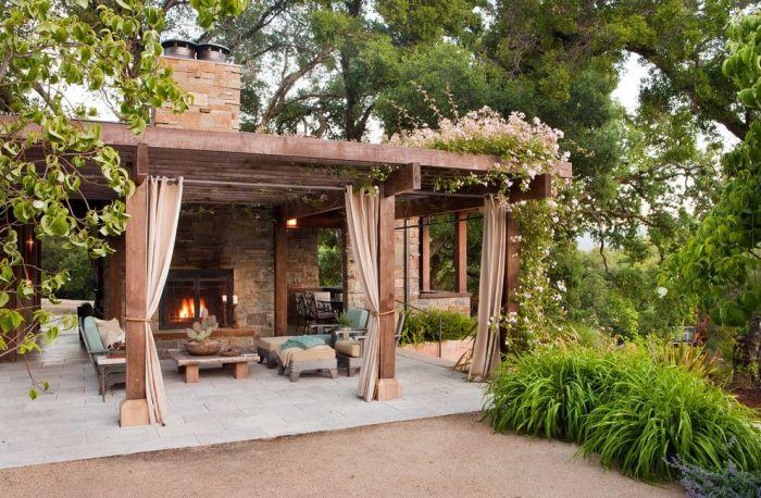Великолепная площадка с массивным каменным камином и элегантной мебелью из светлого дерева.