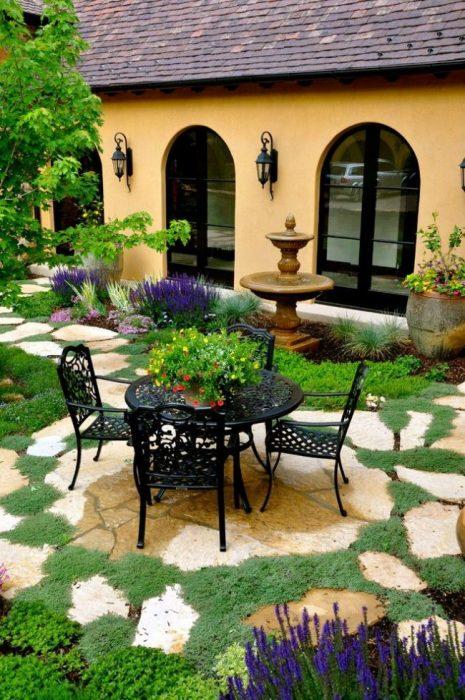Небольшая круглая площадка, вымощенная камнем, которая отлично вписывается в ландшафтный дизайн садового участка.
