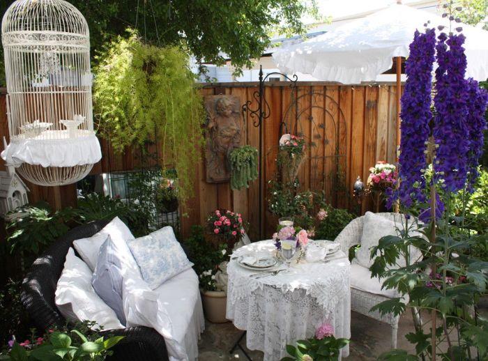 Летнее патио с роскошной садовой мебелью, которое окружено комнатными многолетними растениями.