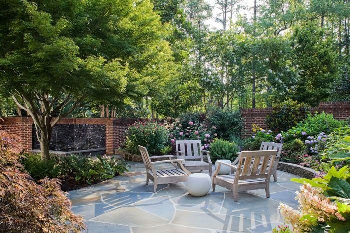Летнее патио с деревянными креслами и маленьким каменным журнальным столиком в окружении зелёного сада.