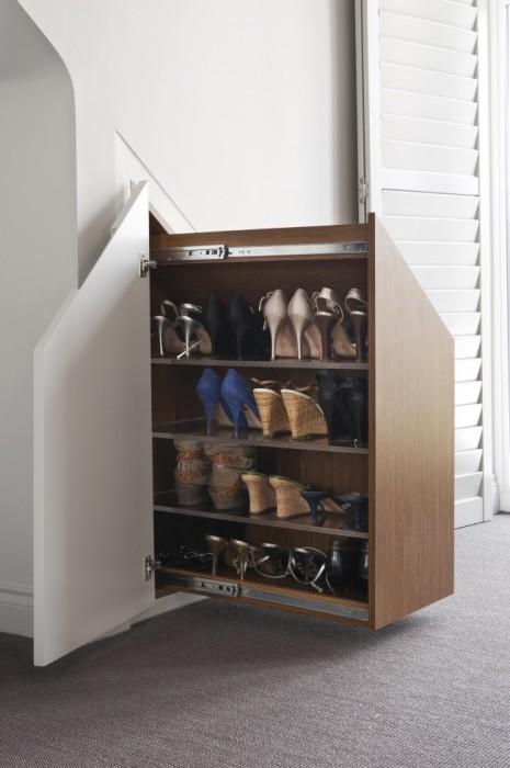 Выдвижной шкаф для обуви, вмонтированный в гипсокартоновую стенку для экономии пространства.