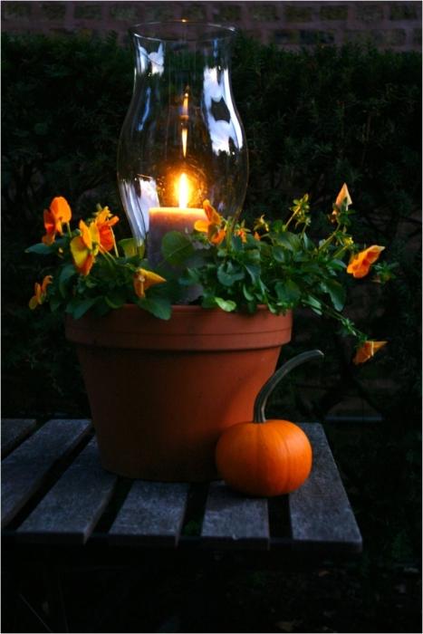 Горшок со свечой, создающий романтическую обстановку в саду.