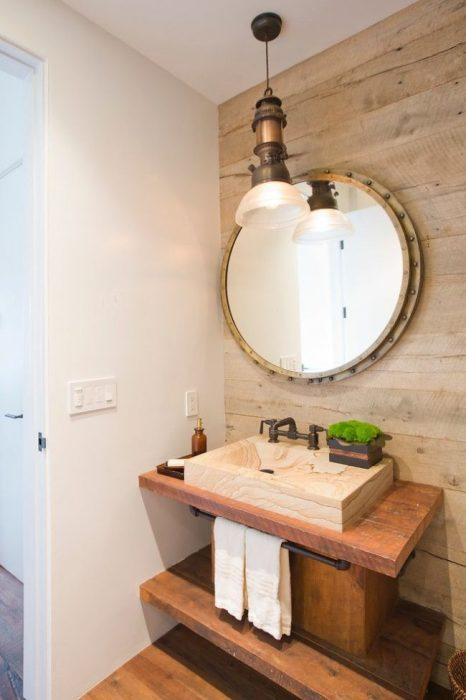 Оригинальная раковина, встроенная в удобную деревянную столешницу с отделением для хранения ванных принадлежностей и металлической трубы, на которую можно повесить полотенце.