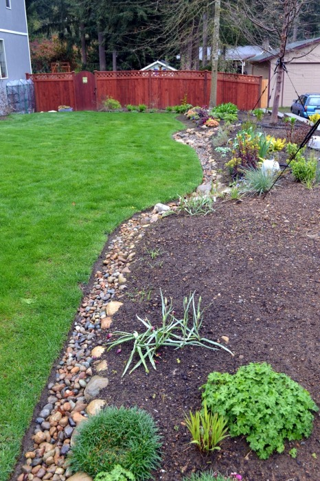Галька в ландшафтном дизайне может служить покрытием для почвы или материалом для создания дорожки.