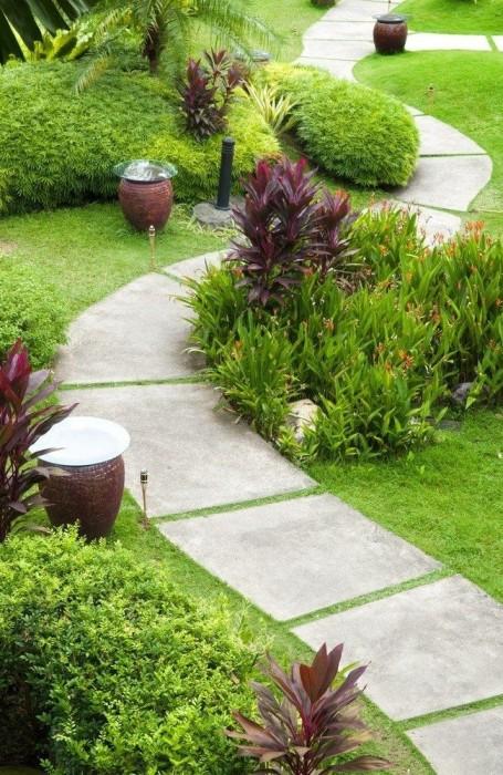 Дорожка из бетонных плит правильной формы на территории садового участка.