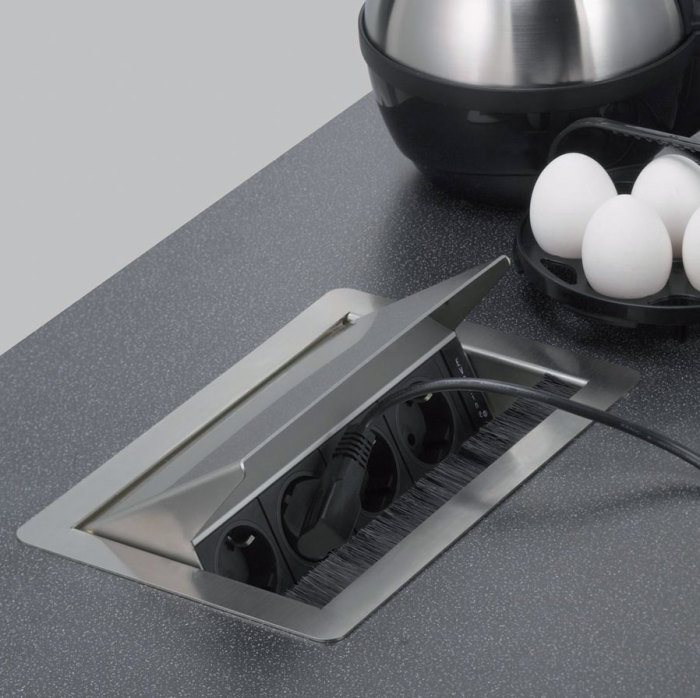 Выдвижные розетки прекрасно встраиваются в любое удобное место на кухне.