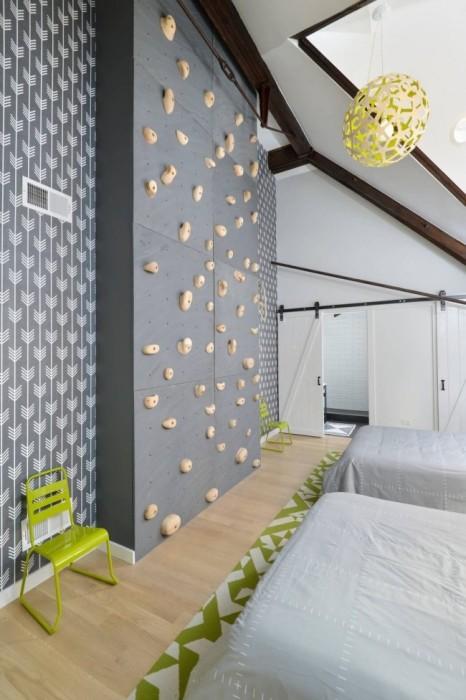 Тренировочная стена для скалолазания в интерьере детской комнаты.