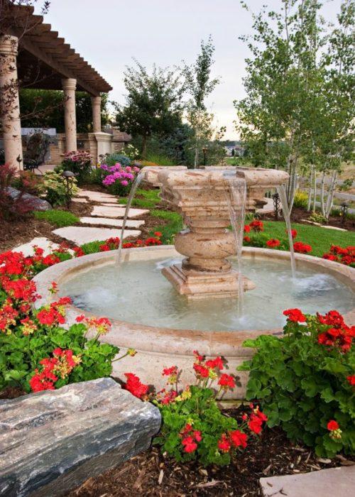 Большой гранитный фонтан в окружении пышных цветов во дворе частного дома.