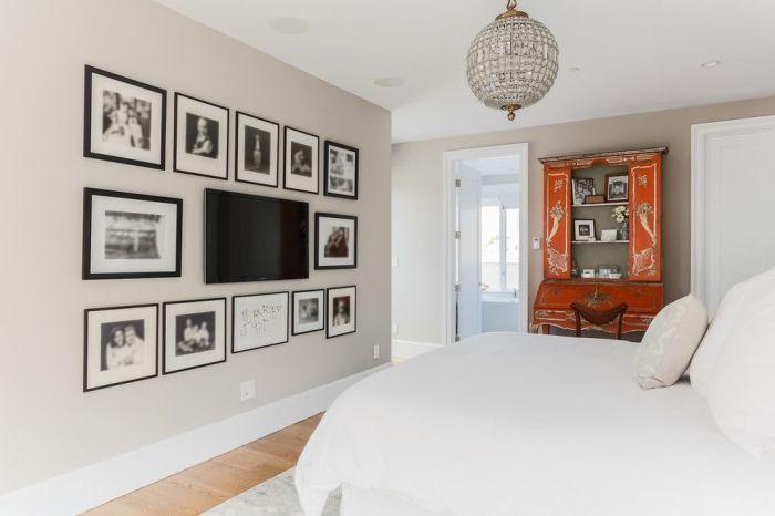 Плазменная панель в центре настенных картин - оригинальная изюминка в спальной комнате.