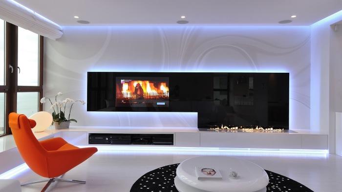 Красивый интерьер гостиной с домашним кинотеатром и большим электрическим камином.