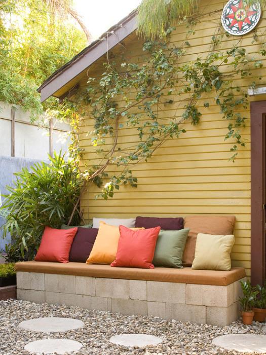 Простой диванчик на территории дачного участка, который можно создать из нескольких шлакоблоков и небольшого матраса.