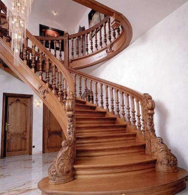 Классическая лестница из темной породы древесины ведущая на второй этаж.