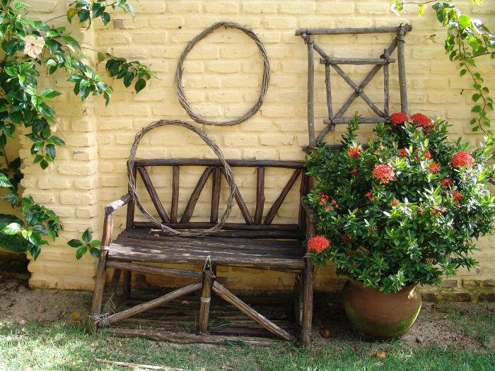 Деревянная скамейка из темной породы древесины для садового участка.