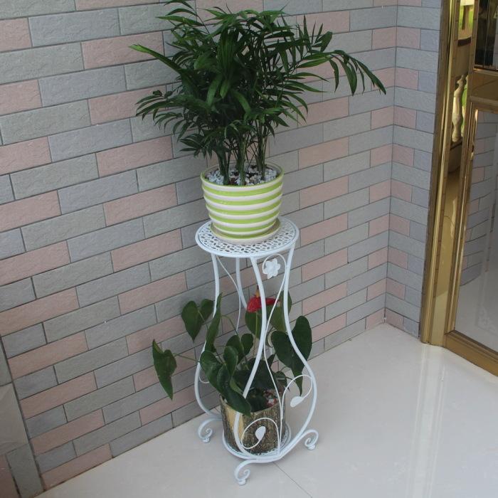 Белая кованая подставка для цветов - необычное дизайнерское решение.