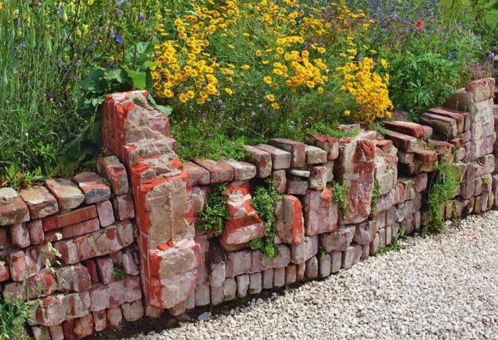 Ограждение, сделанное из старых кирпичей и массивных фрагментов кирпичной кладки.