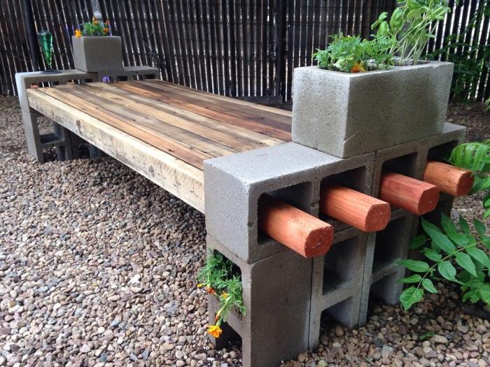 Оригинальная идея смонтировать лавочку из дерева и шлакоблоков для приятного отдыха в саду.