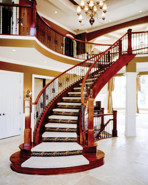 Аристократическая деревянная лестница ведущая на второй этаж в интерьере дома.