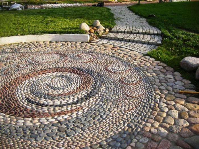 Дорожка в виде мозаики, выложенная из мелкой морской гальки на территории садового участка.