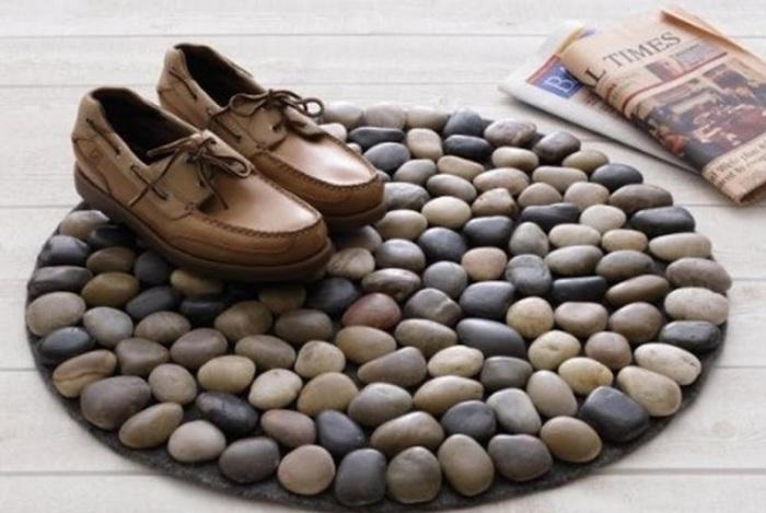 Небольшой коврик, декорированный морскими камушками, который служит для вытирания обуви.