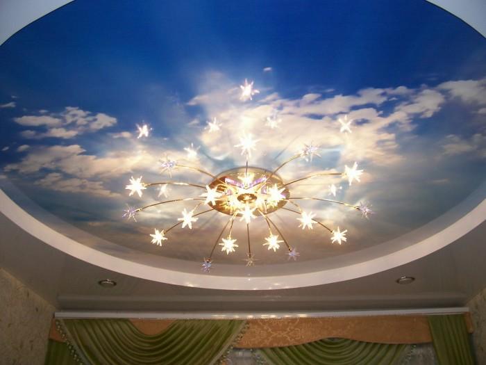 Необычный натяжной потолок с фотопечатью в виде неба, который создает теплую атмосферу.
