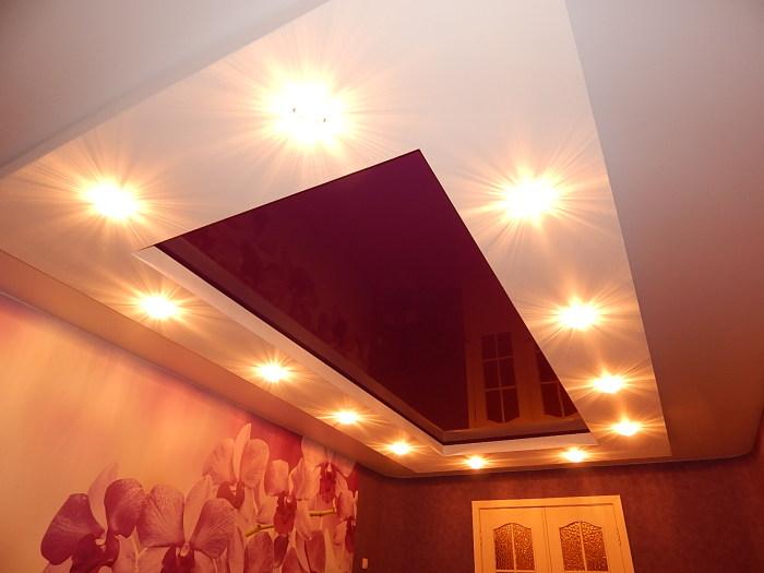 Красный натяжной потолок и романтическое освещение создаст отличную атмосферу в комнате.