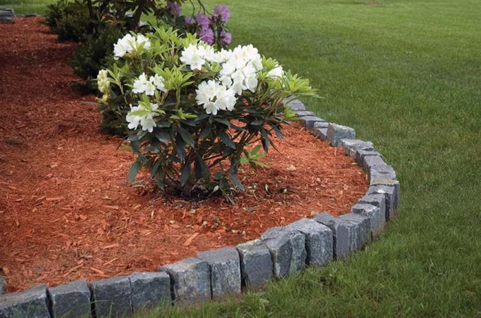 Цветник, который хорошо выделяется на фоне зелёного газона станет отличным украшением на участке.