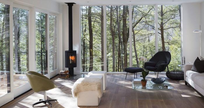 Чугунная буржуйка, которая гармонично смотрится в современном интерьере гостиной комнаты.