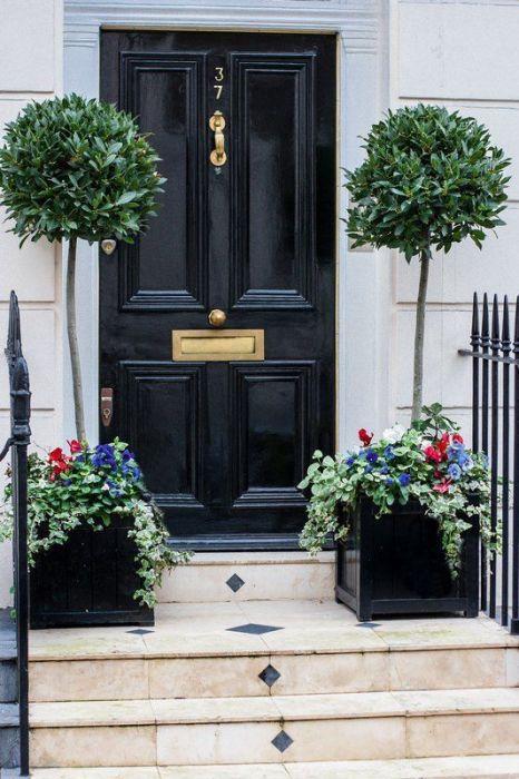 Вход в дом, оформленный парой оригинальных вазонов по обе стороны дверей.