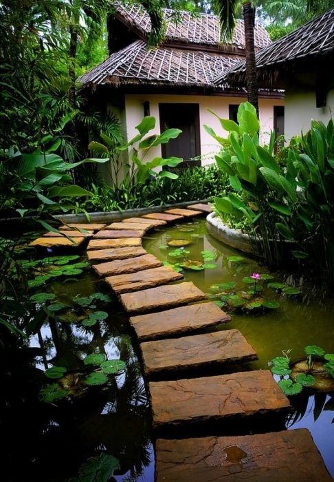 На территории загородного участка хорошо будет смотреться деревянная дорожка на металлических опора, которая расположена над поверхностью искусственного водоема с лилиями.