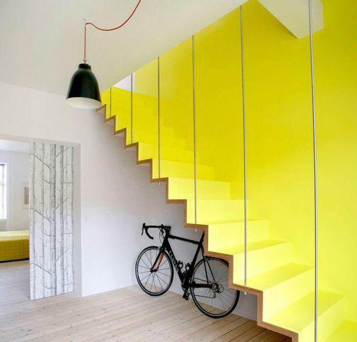 Яркая деревянная лестница лимонного цвета с тонкими стеклянными перилами.