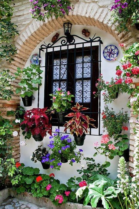Необычную композицию можно создать при помощи декоративного окна и разноцветных кашпо с цветами.