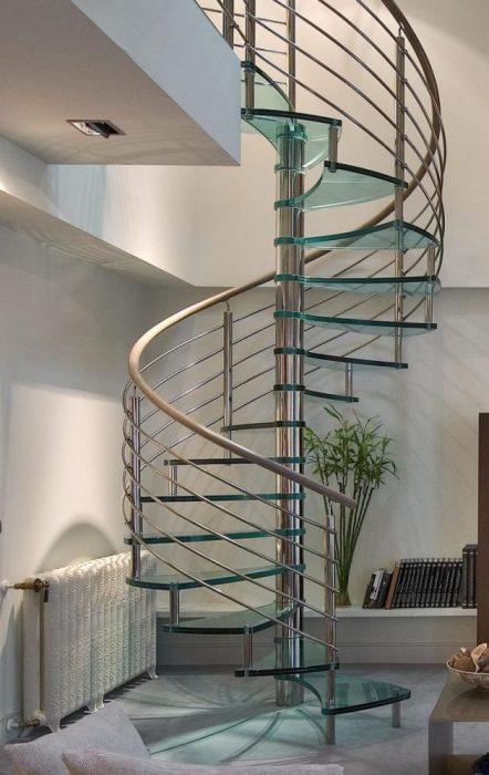 Классическая винтовая лестница с металлическими перилами и стеклянными ступеньками.